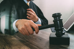 Justice and law concept.Male judge in a courtroom striking the g. Avel,working with digital tablet computer docking keyboard on wood table,filter effect Stock Image