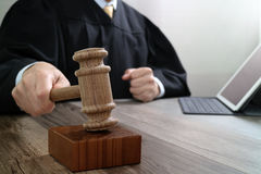 Justice and law concept.Male judge in a courtroom striking the g. Avel,working with digital tablet computer docking keyboard on wood table Stock Photography