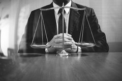 Justice and law concept.Male lawyer in the office with brass scale on wooden table,black and white stock photography