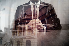 Justice and law concept.Male lawyer in the office with brass scale on wooden table with london city background,double exposure royalty free stock images