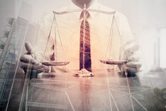 Justice and law concept.Male lawyer in the office with brass scale on wooden table with london city background,double exposure stock images