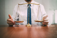 Justice and law concept.Male lawyer in the office with brass scale on wooden table,reflected view stock photos
