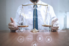Justice and law concept.Male lawyer in the office with brass sca. Le on wooden table,virtual graphic icons screen diagram Royalty Free Stock Photography