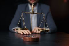 Justice and law concept.Male lawyer in the office with brass scale on wooden table,reflected. View royalty free stock images