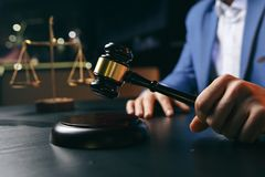 Justice and law concept.Male lawyer in the office with brass scale on wooden table,reflected. View stock photography
