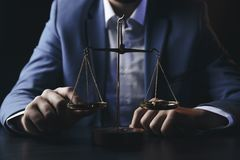Justice and law concept.Male lawyer in the office with brass scale on wooden table,reflected. View stock photo