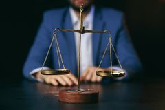 Justice and law concept.Male lawyer in the office with brass scale on wooden table,reflected. View royalty free stock photos