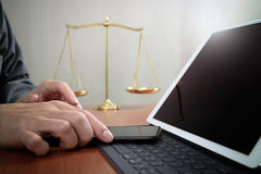 Justice and law concept.Male lawyer in office with the gavel,working with smart phone and digital tablet computer and brass scale. On wood table royalty free stock photography