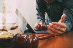 Justice and law concept.Male lawyer in office with the gavel,working with smart phone and digital tablet computer and brass scale. On wood table stock image