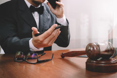 Justice and law concept.Male lawyer in office with the gavel,wor. King with smart phone,digital tablet computer docking keyboard,brass scale,on wood table,filter Stock Photo
