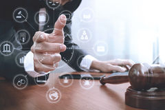 Justice and law concept.Male lawyer in office with the gavel,wor. King with smart phone,digital tablet computer docking keyboard,brass scale,on wood table Royalty Free Stock Image