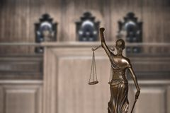 Lady justice and empty bench with judge chairs in courtroom royalty free stock photography