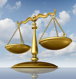 Justice Scale. Of law made of chrome metal on a sky background as a symbol of the legal system in government and society in enforcing rights and regulations Royalty Free Stock Image