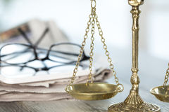 Justice scale with eyeglasses, newspaper and tablet Stock Photo