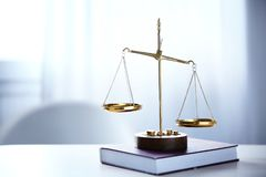 Justice scales and book on table in room. Justice scales and book on table in the room royalty free stock images