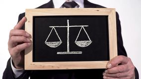 Justice scales drawn on blackboard in lawyer hands, decision pros and cons. Stock footage stock illustration