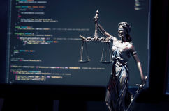 Justice statue with code on monitor device in background. Programming code law crime justice internet statue themis concept royalty free stock photo