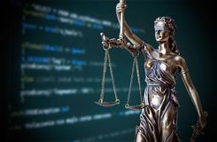 Justice statue with code on screen in background Stock Photos