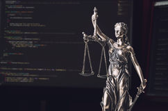 Justice statue with code on screen in background Royalty Free Stock Photography