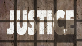 Justice On A Wall With Jail Bars Shadow. Justice Written On A Wall With Jail Bars Shadow Stock Image