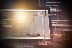Justice weight scales with code on monitor in background Stock Photography