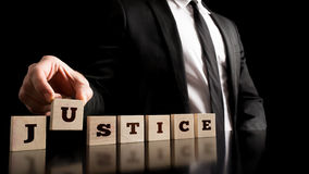 Justice on Wooden Piece Arranged by Businessman Royalty Free Stock Photography