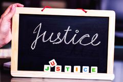 JUSTICE WRITTEN ON A CHALK BOARD WITH CHALK AND LETTERS stock photography