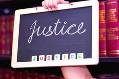 WOMEN HAND HOLDING CHALK BOARD ON WHICH JUSTICE IS WRITTEN stock photography