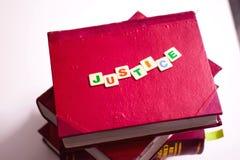 JUSTICIA ESCRITA EN LOS LIBROS DE LEY ROJOS imagen de archivo libre de regalías