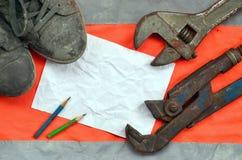 Justierbare Schlüssel mit alten Stiefeln und ein Blatt Papier mit zwei Bleistiften Stillleben verband mit Reparatur, Eisenbahn od Stockfotos