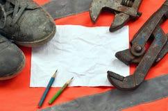 Justierbare Schlüssel mit alten Stiefeln und ein Blatt Papier mit zwei Bleistiften Stillleben verband mit Reparatur, Eisenbahn od Stockbilder