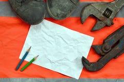 Justierbare Schlüssel mit alten Stiefeln und ein Blatt Papier mit zwei Bleistiften Stillleben verband mit Reparatur, Eisenbahn od Stockbild
