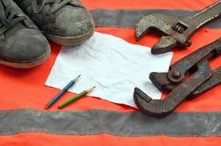 Justierbare Schlüssel mit alten Stiefeln und ein Blatt Papier mit zwei Bleistiften Stillleben verband mit Reparatur, Eisenbahn od Lizenzfreies Stockfoto