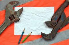 Justierbare Schlüssel und ein Blatt Papier mit zwei Bleistiften Stillleben verband mit Reparatur, Eisenbahn oder Installationsarb Stockfoto