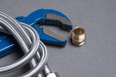 Justierbarer Schlüssel, Nippel und umsponnener Edelstahl wässern Schlauch Lizenzfreie Stockfotografie