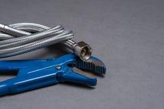 Justierbarer Schlüssel und umsponnener Edelstahlwasserschlauch Lizenzfreie Stockfotos