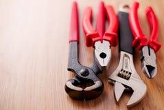 Justierbarer Schlüssel, Zangen, Tischlerhammer und Zangen auf dem hölzernen Hintergrund Lizenzfreies Stockfoto