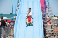 Justin Trudeau and Hadrien on slide. Justin Trudeau, prime minister of Canada, goes down a carnival ride with his son, Hadrien, with big smiles royalty free stock photos