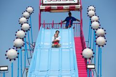 Justin Trudeau riding down slide. Justin Trudeau, prime minister of Canada, goes down a carnival ride with his son, Hadrien, with big smiles stock photo