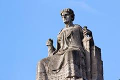 Justitia en su trono antes de un cielo azul claro imágenes de archivo libres de regalías