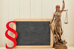 Justitia next to blackboard background as law concept stock photography