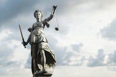 Justitia symbol av rättvisa framme av bakgrund med himmel och c royaltyfri foto