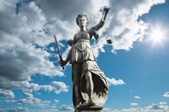 Justitia symbol of justice in front of background with sky and c royalty free stock photography