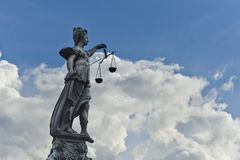 Justizia. Statue of Justice with sword and scales in front of a blue cloudy sky stock photos