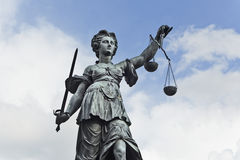 Justizia. Statue of Justice with sword and scales in front of a blue cloudy sky royalty free stock photo