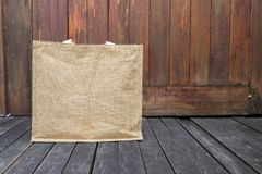 Jute bag on wooden floor with space on wood background. Eco friendly bag, grocery shopping bag stock photography