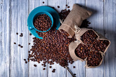 Jute bags with coffee beans and blue cup. Stock Photo