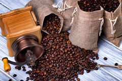 Jute bags with coffee beans and grinder Royalty Free Stock Photos