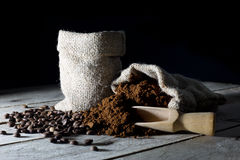 Jute Bags Filled with Ground Coffee and Coffee Beans on an Old Rustic Wooden Table on Black Stock Photos