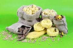Jute Bags Filled with Pasta of Different Colors and Shapes On Green Background Royalty Free Stock Photo